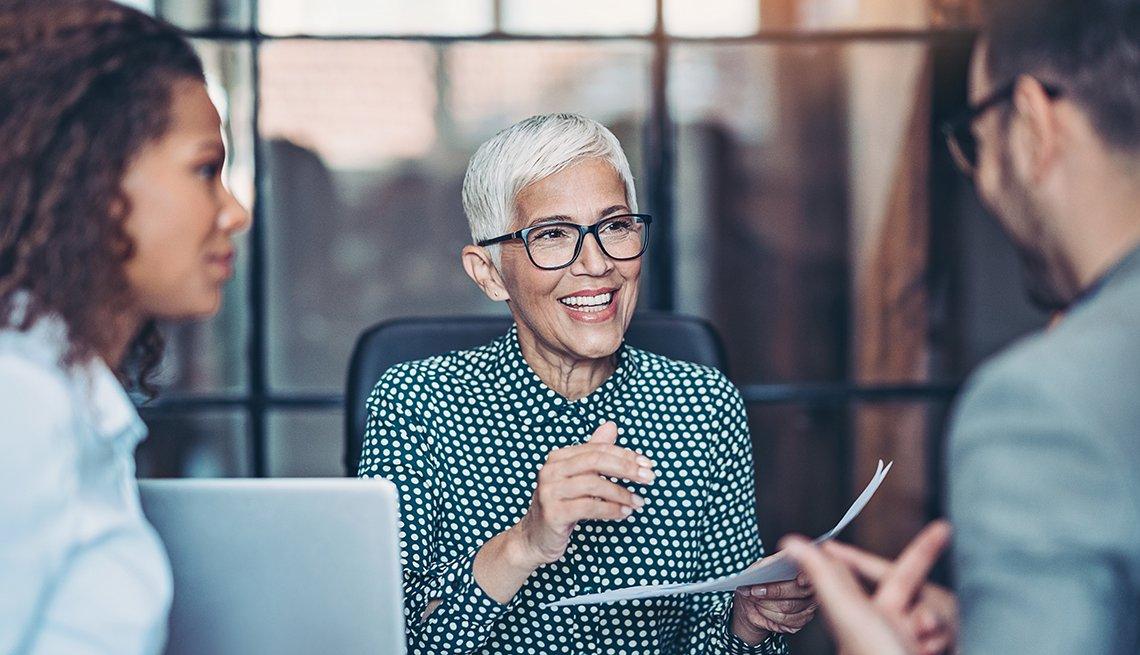 Mujer mayor hablando en una oficina con una mujer y un hombre.