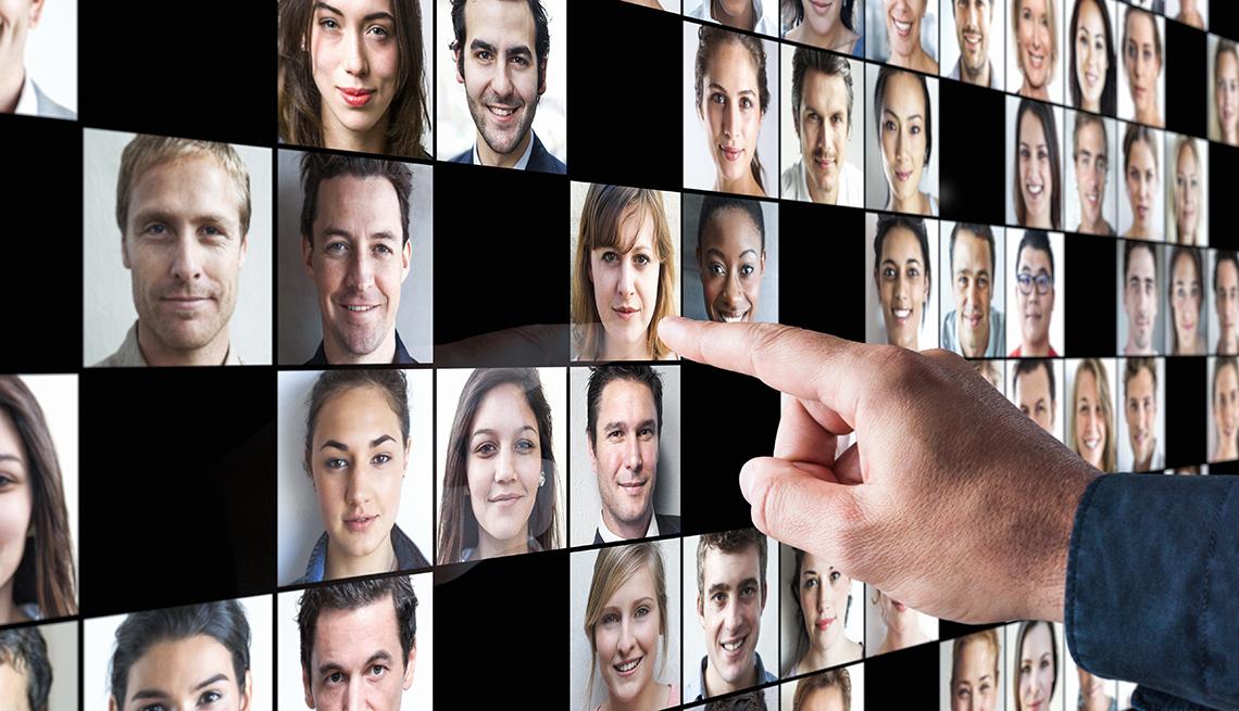 Persona señalando a una mujer en una pantalla con otros rostros.