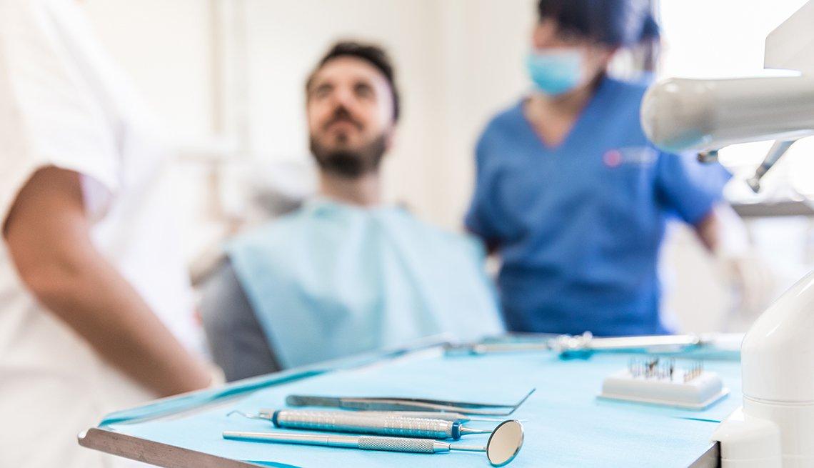 Dentista, una asistente y un paciente en un consultorio dental