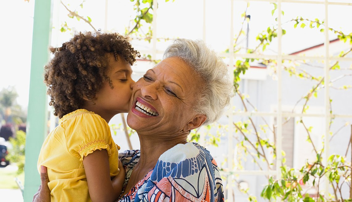 A woman being kissed on the cheek by her grandchild