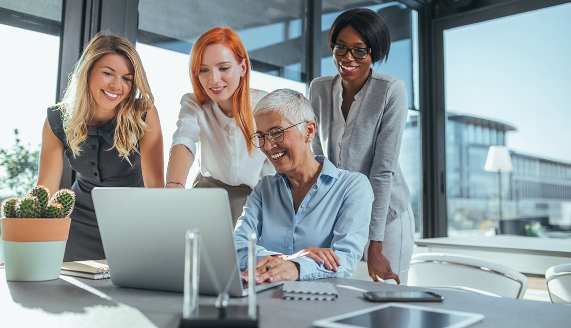 Mujeres viendo una computadora en una oficina