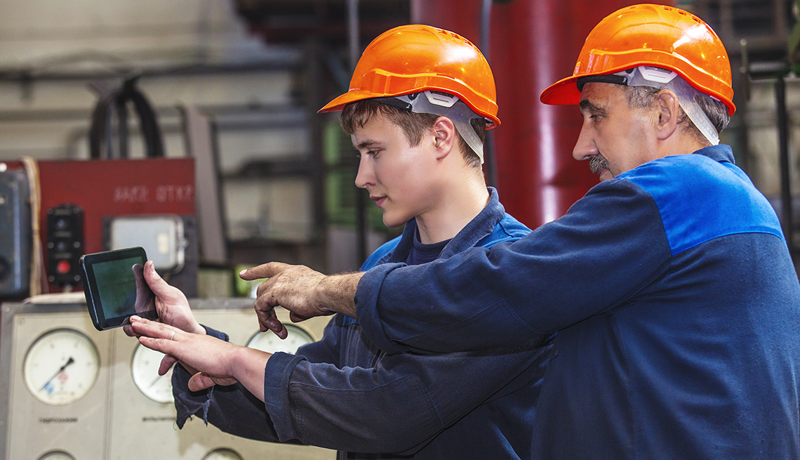 Hombre mayor monitorea el trabajo de uno más joven en un fábrica