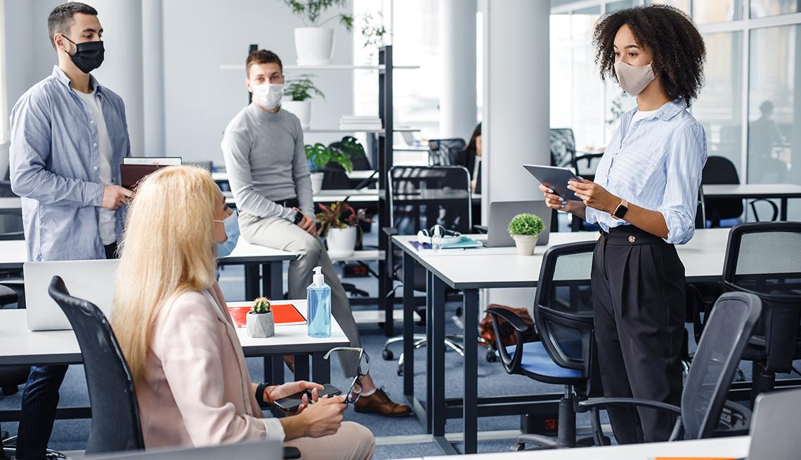 Cuatro personas con mascarilla y con la distancia social de la pandemia en un salón de reuniones.