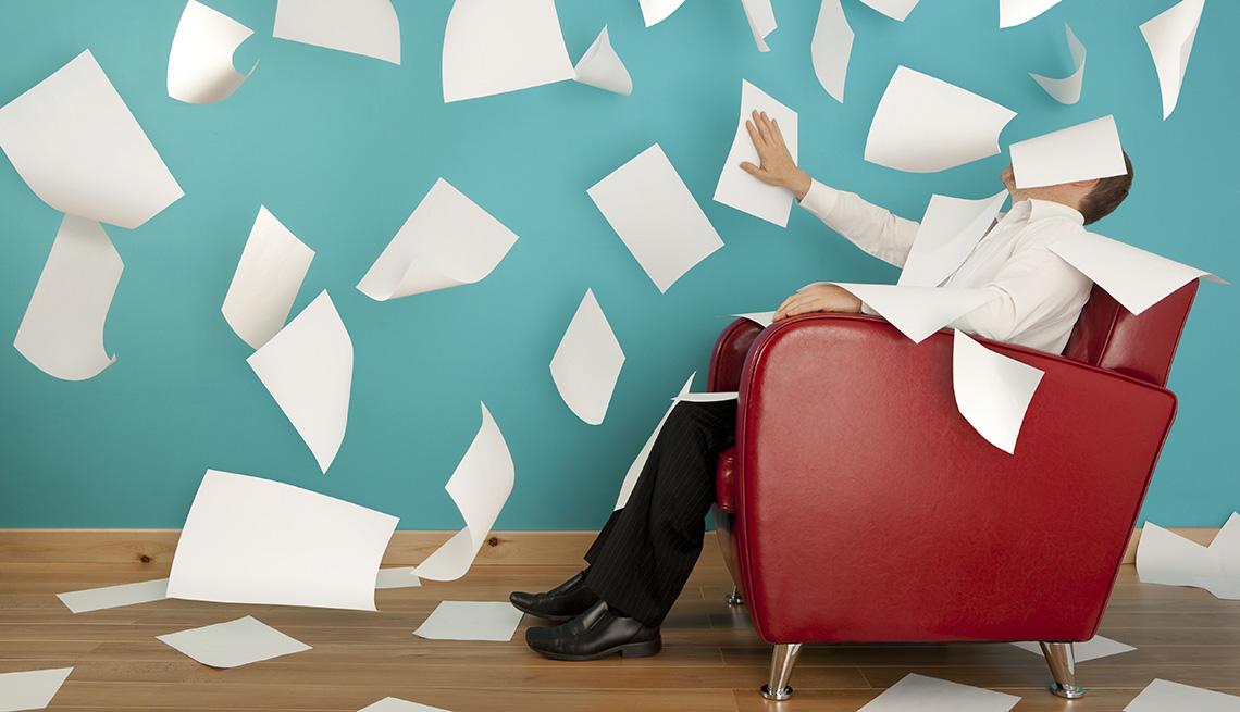 Hombre sentado en una silla roja con decenas de hojas de papel en el aire, quizás aprendiendo las nuevas reglas de la carta de presentación.