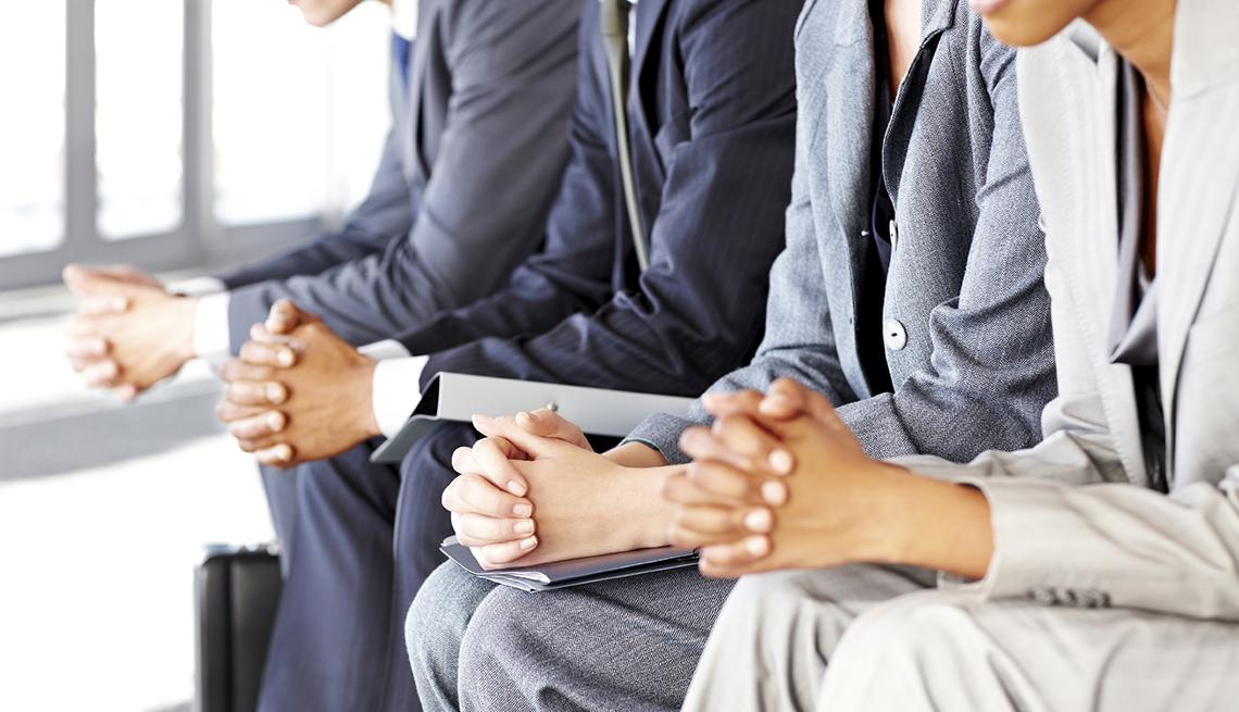 Gente de negocios sentada nerviosa con las manos cruzadas