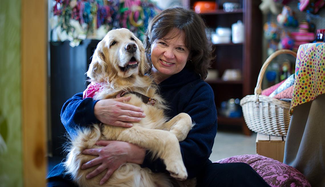Linda Waitkus abraza a un perro labrador, como uno de los trabajos para amantes de animales.