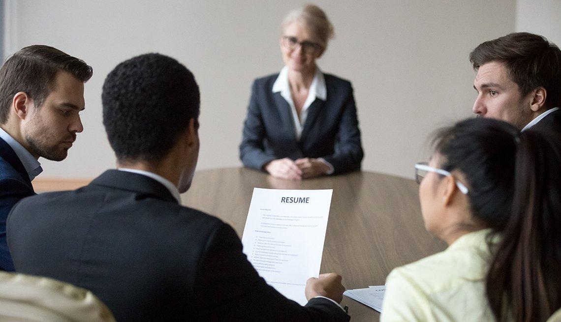 Mujer mayor siendo evaluada por reclutadores de empleo.