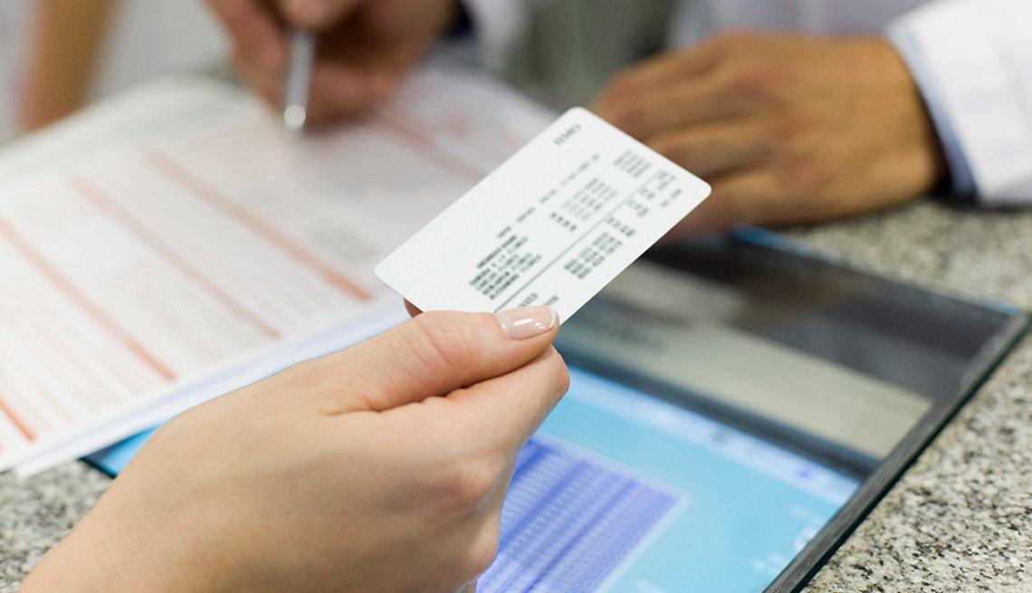 Persona sosteniendo una tarjeta de seguro médico.