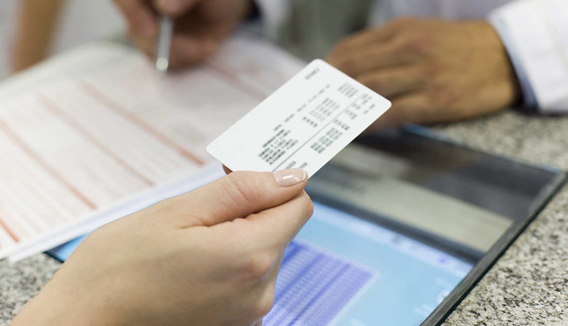 a person holds a health insurance card