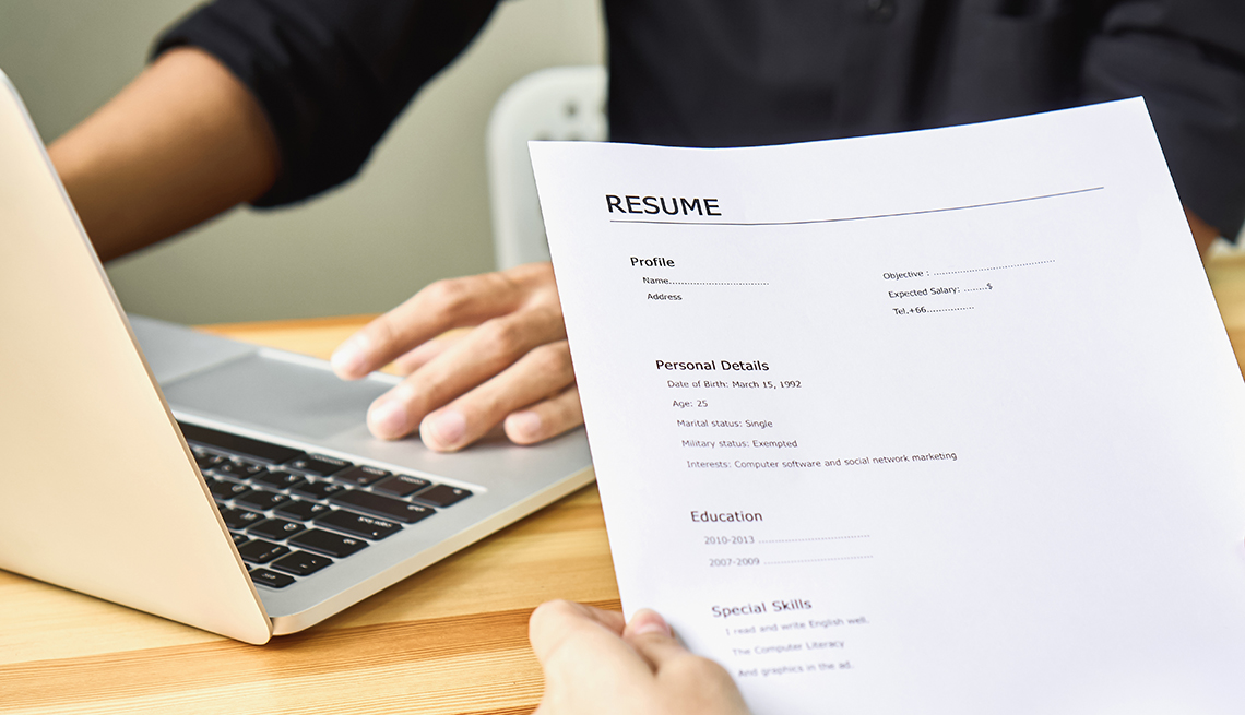 person holds a resume in front of a laptop