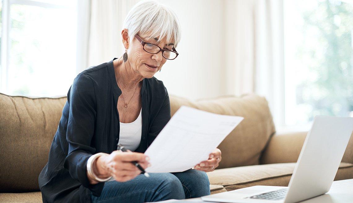 Mujer mirando una hoja de vida y con su computadora en una mesa de sala.