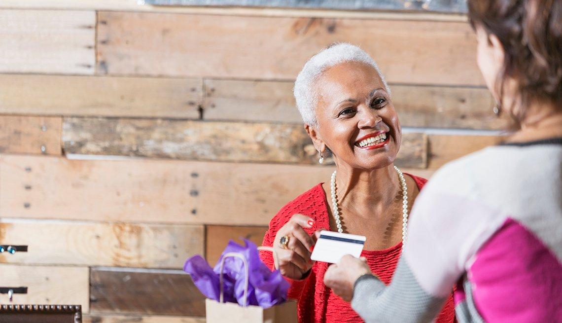 Cajera en una tienda toma la tarjeta de una mujer.