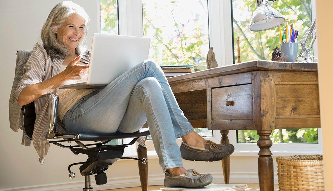 Mujer sentada frente a su escritorio y con una computadora sobre las piernas.