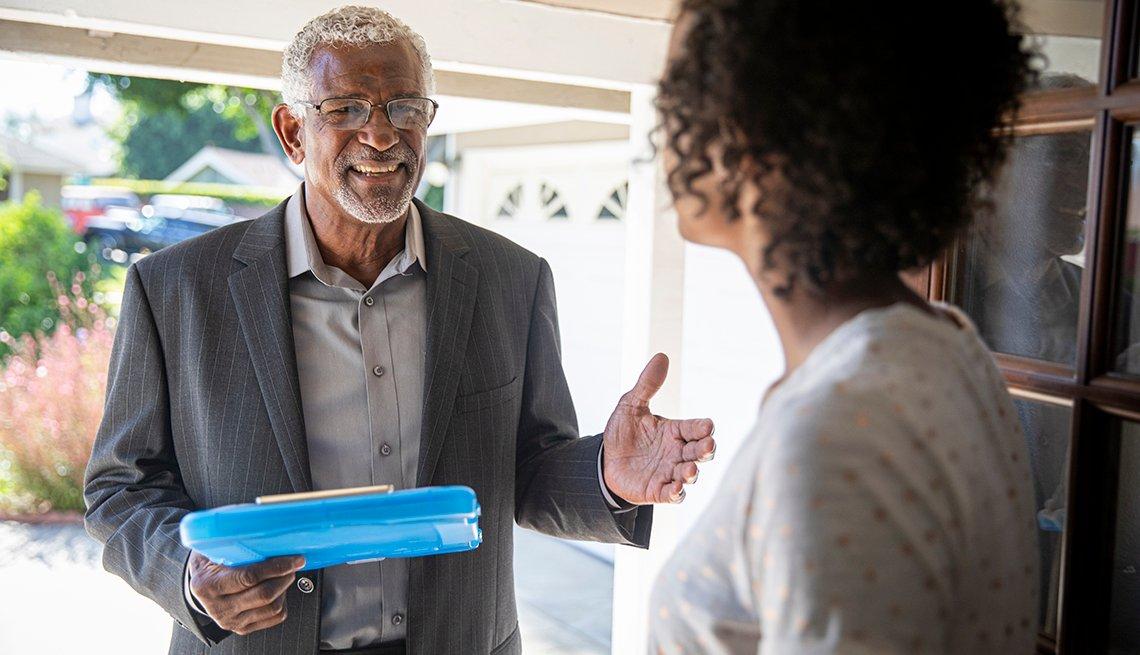 Hombre mayor visita a una mujer en la puerta de su casa.
