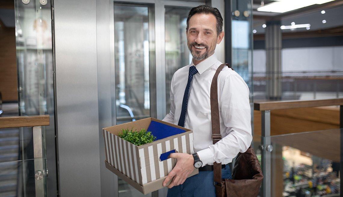 Hombre sosteniendo una caja con objetos personales cerca al elevador de una oficina.