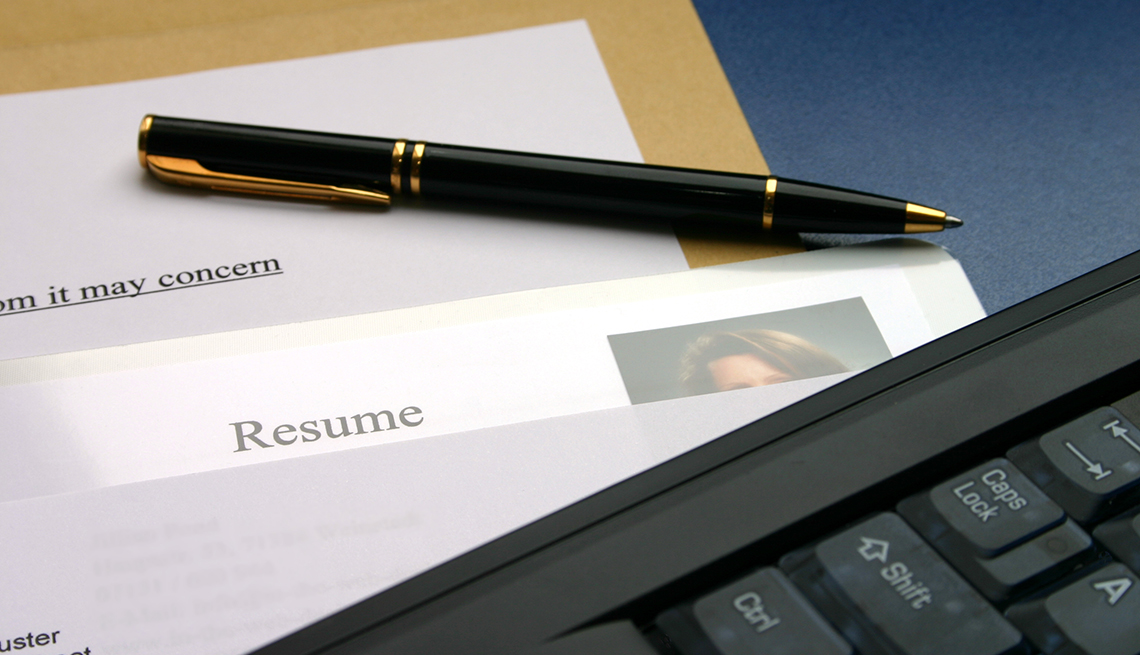 A resume and cover letter on a desk with a computer and pen