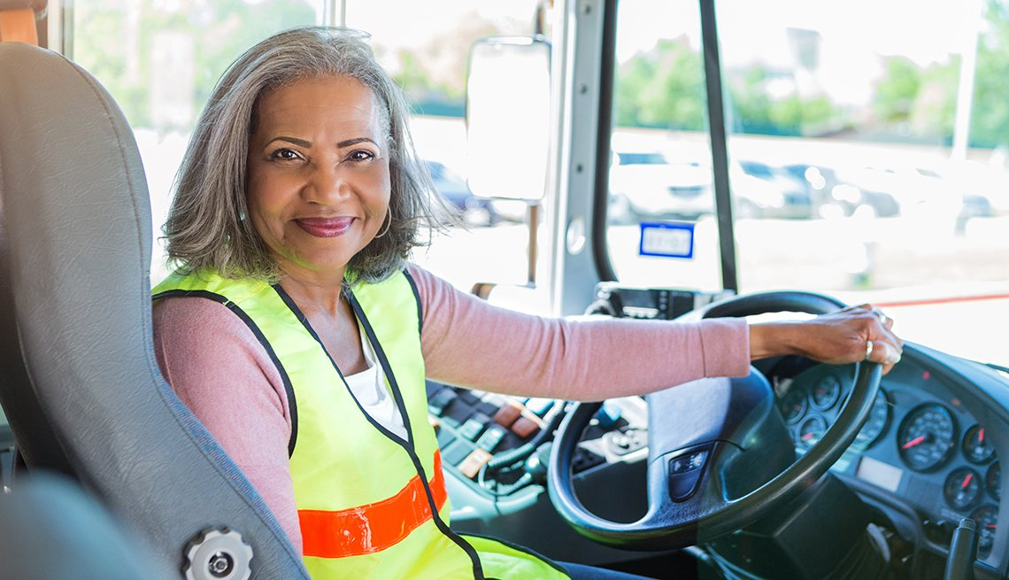 smiling senior female bus driver turns to look at the camera from the driver's seat of her school bus