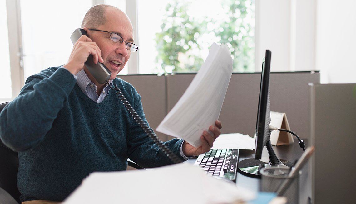 mature man speaks on the desk phone in an office about account receivable