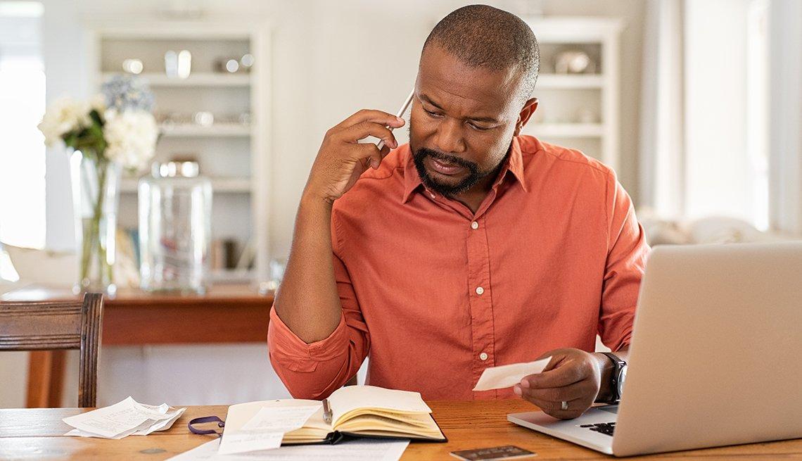 Hombre sentado mirando recibos y una agenda frente a una computadora portátil.