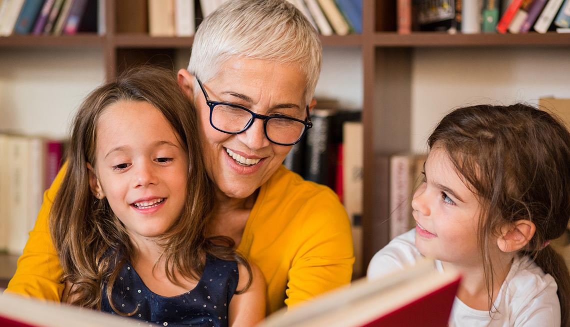 Mujer mayor leyendo un libro a dos niñas.