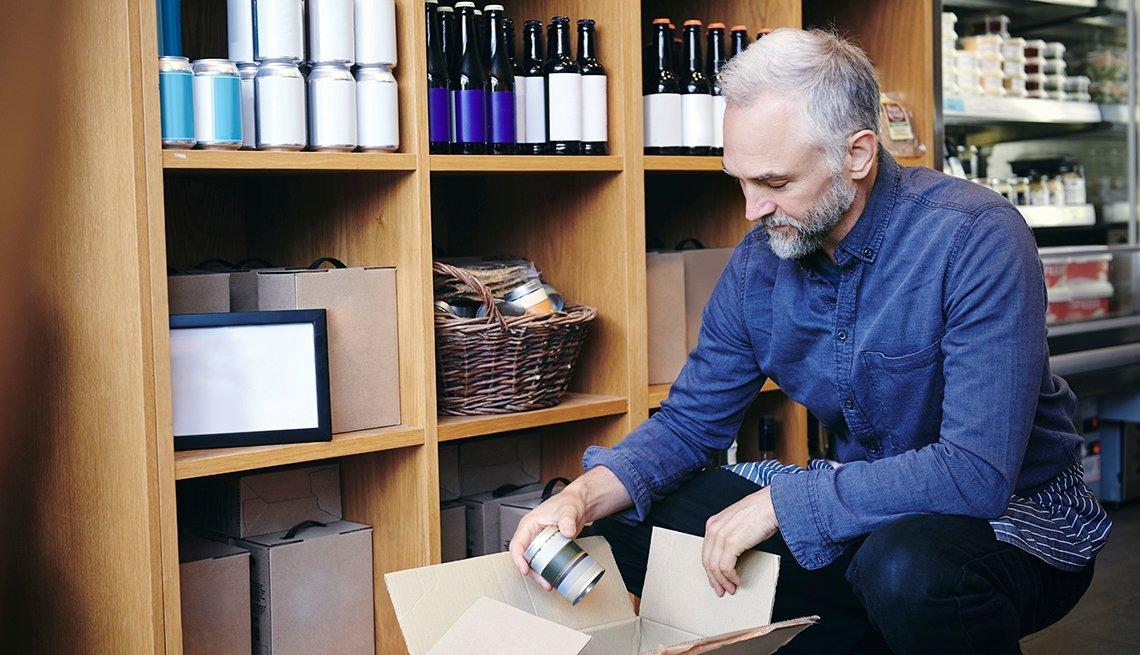 Hombre mayor empacando productos de un mueble.