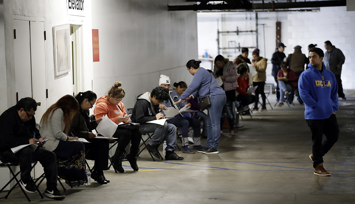 Personas llenando los formularios para los beneficios del desempleo, Los Ángeles, California.