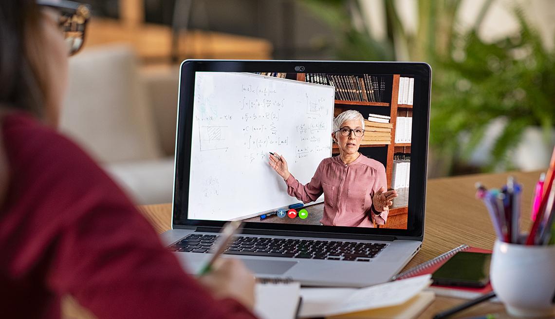 Mujer viendo una clase en línea en su casa.