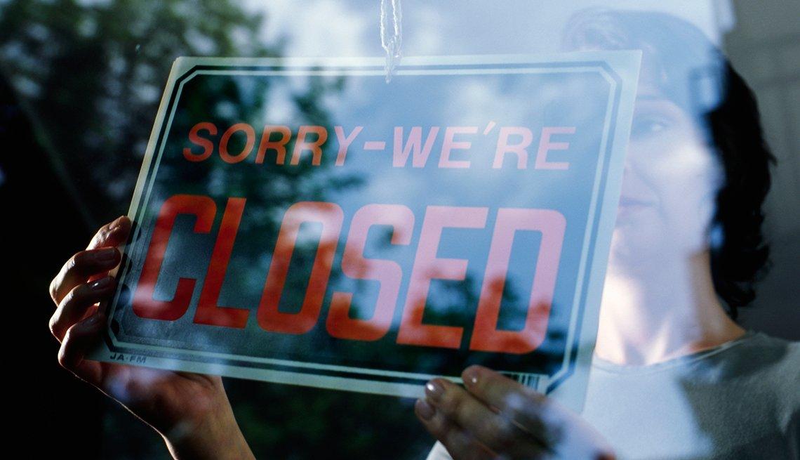 Mujer girando un letrero en una tienda que dice, 'disculpe, hemos cerrado'.
