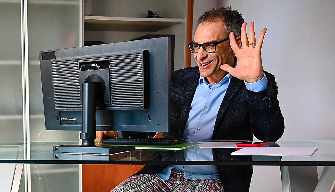 Hombre con pantalón de pijama, camisa y saco de corbata frente a una computadora.