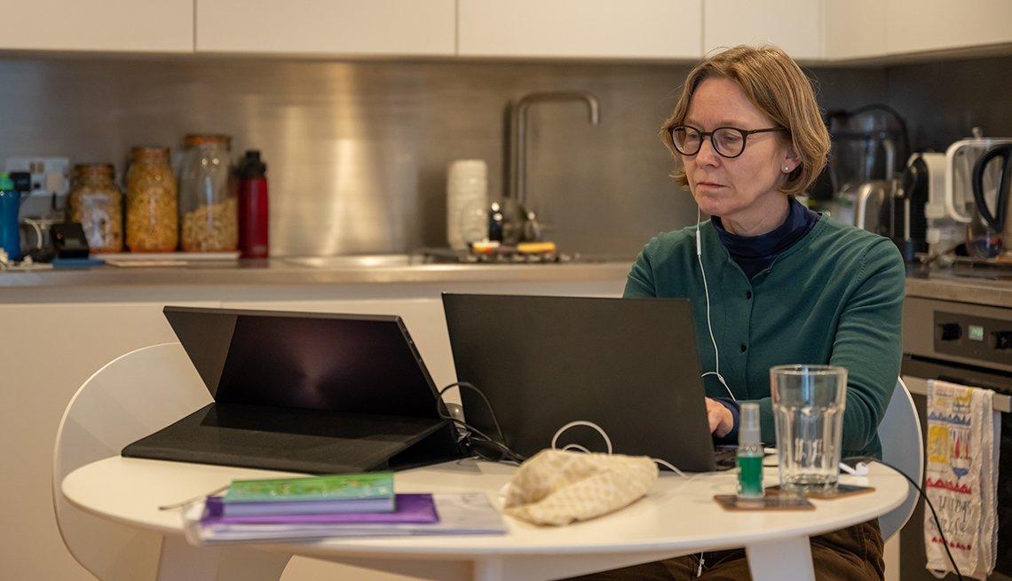 Mujer con dos computadoras en la cocina de su casa durante la pandemia.