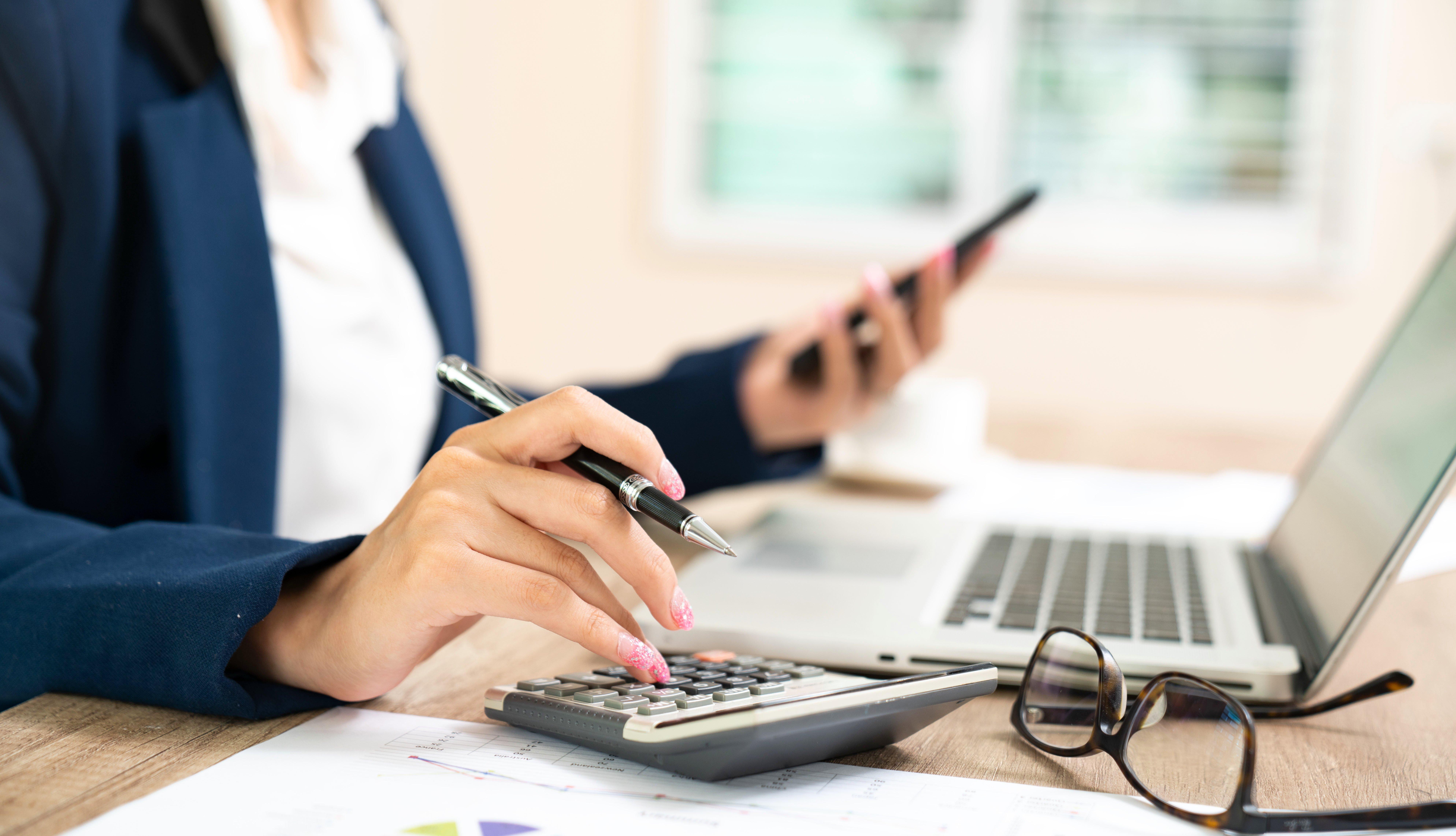 Mujer trabajando con una calculadora, un celular en la mano y frente a una computadora.