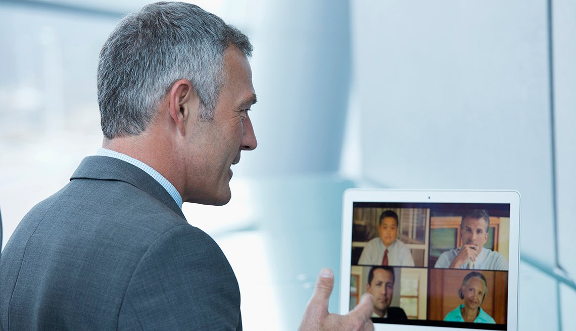 Hombre en traje de corbata desde su casa y haciendo una videoconferencia con otros colegas.