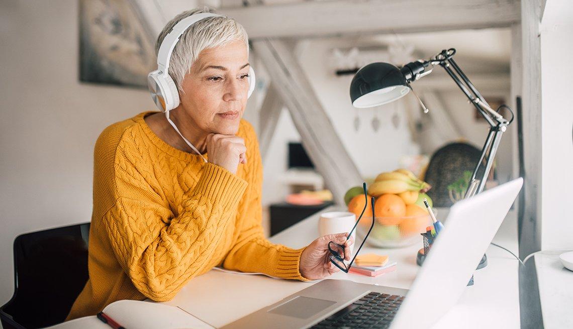 Mujer en su casa sentada en un escritorio y frente a la computadora.