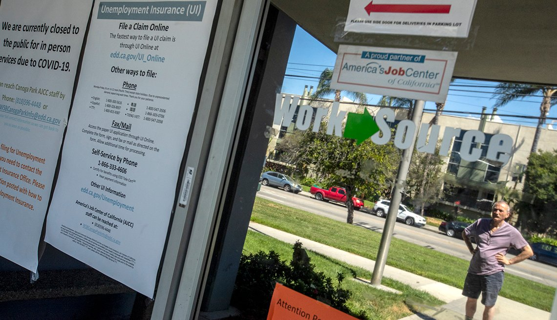 Un hombre lee anuncios en la ventana del Departamento del Desarrollo del Empleo del estado de California, el cual se encuentra cerrado.