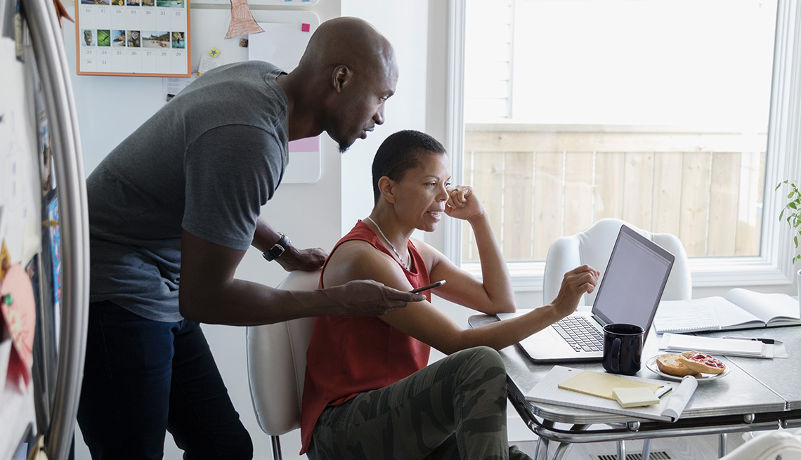 A husband and wife looking at their finances on a laptop in their kitchen