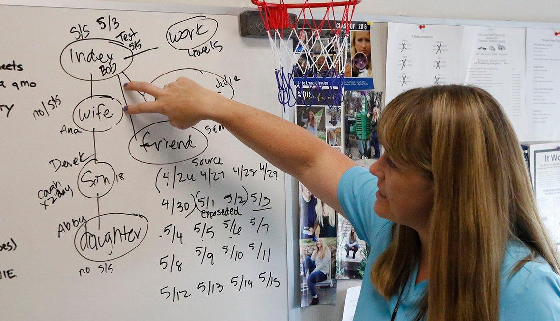La enfermera Lee Cherie Booth señala un tablero donde enseña a los nuevos rastreadores de contactos.
