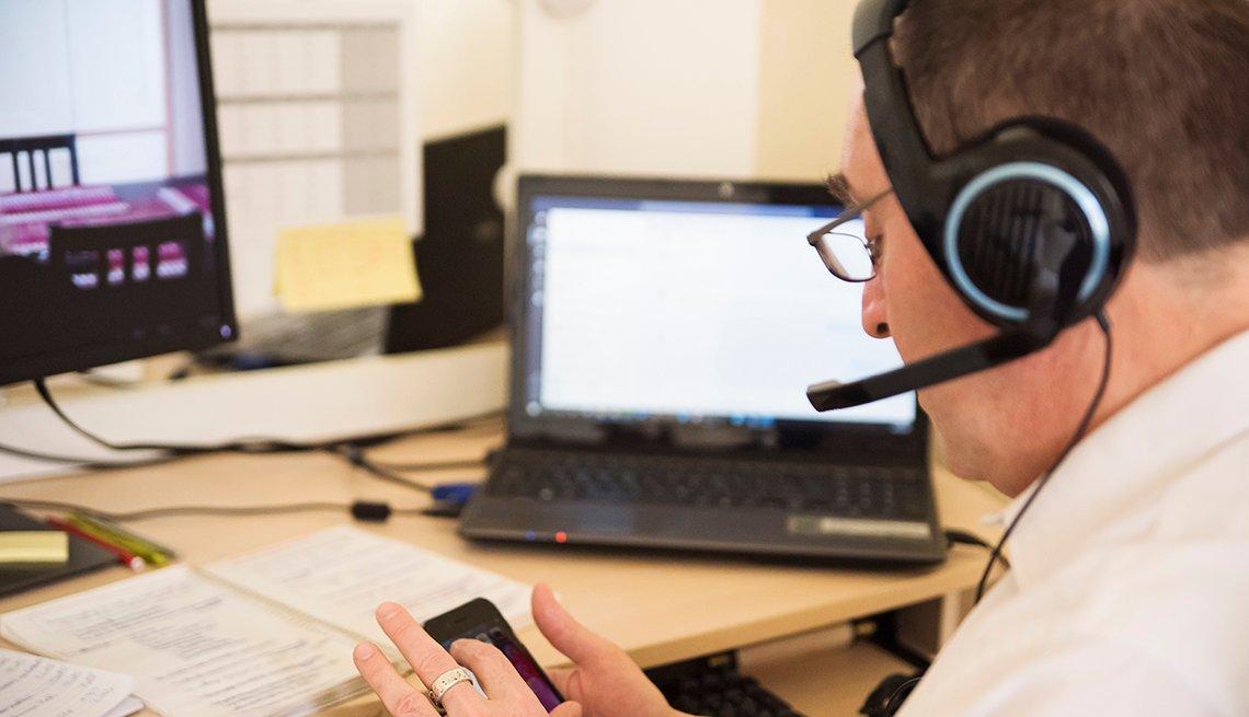 Hombre trabajando desde su casa con una computadora, un teléfono, un sistema de auricular y micrófono.