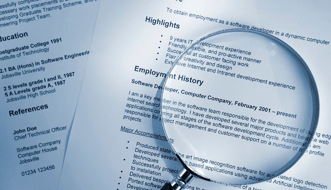 A resume with a magnifying glass on top of it