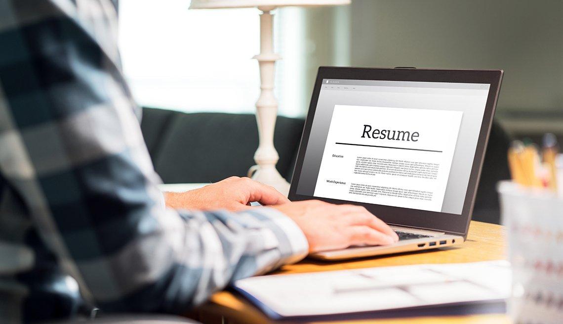 Hombre sentado frente a una computadora personal revisando su hoja de vida.