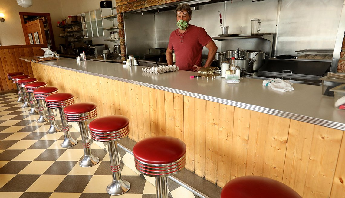 A worker stands behind the counter at an empty restaurant