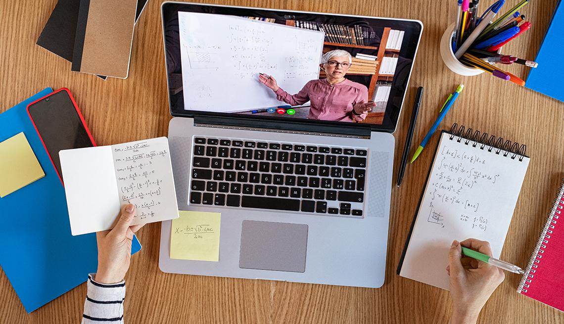 Manos de una persona quien toma una clase en línea desde su computadora.