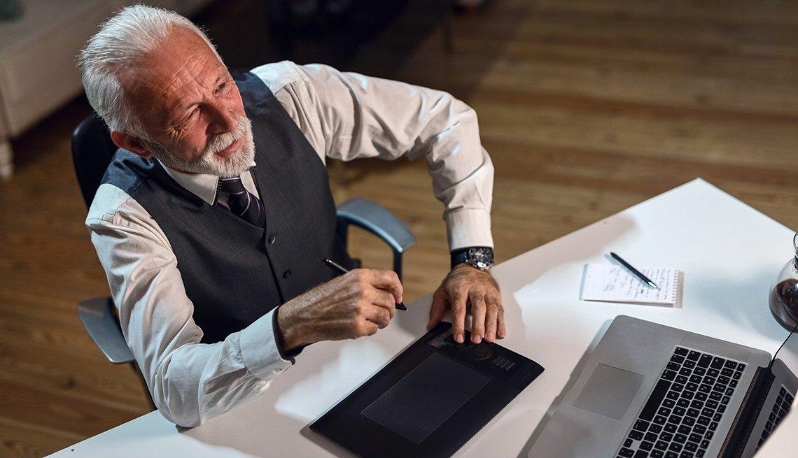 Hombre mayor sentado frente a un escritorio y viendo su computadora.