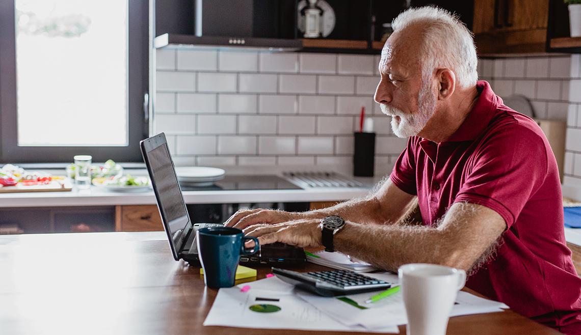 Hombre trabajando en su computadora en la cocina de su casa.