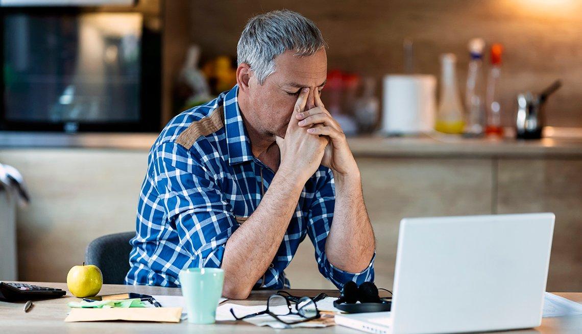 Man stressed looking at laptop