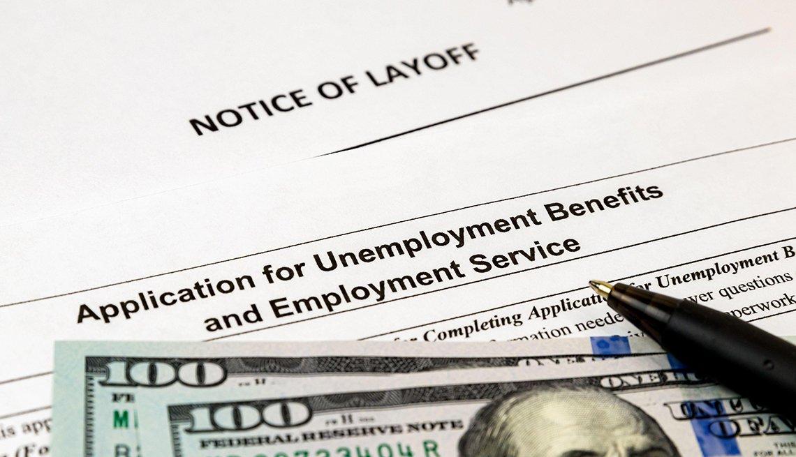 Notificación de despido, formulario de beneficios de desempleo y dos billetes de 100 dólares.