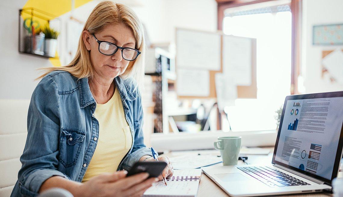 Mujer mira su teléfono mientras está sentada frente a la computadora en su casa.