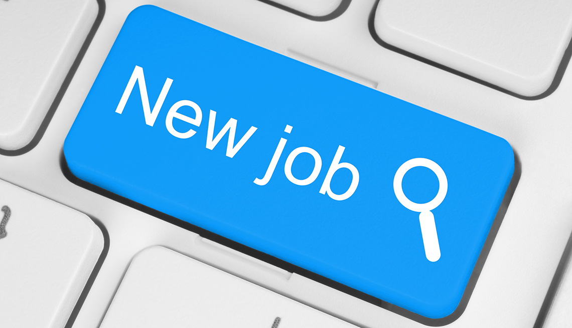 A blue button on a white keyboard with the word new job