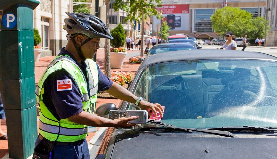 Agente de tránsito colocando un tiquete en un carro.