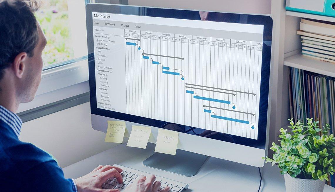 Hombre mirando una tabla de tareas en su computadora.