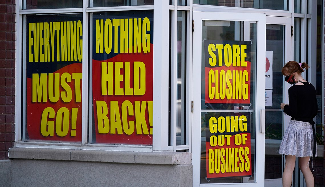 A woman stands at the doorway of a store that is going out of business
